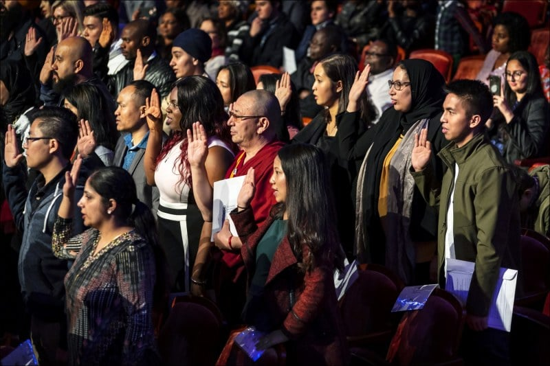 Some 98 new United States citizens, including Burmeese Chin, take the oath of citizenship before U.S. District Court Judge Robyn Moberly at the Palladium Center for the Performing Arts in Carmel, Indiana.  Twenty-five year old Cdin Thanga Cherput (green jacket lower left) was among five Chin visible in this photograph.