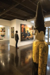 A man walks through a gallery while looking at art