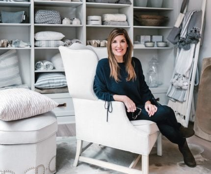A woman sits in an oversized white chair surrounded by interior design products.
