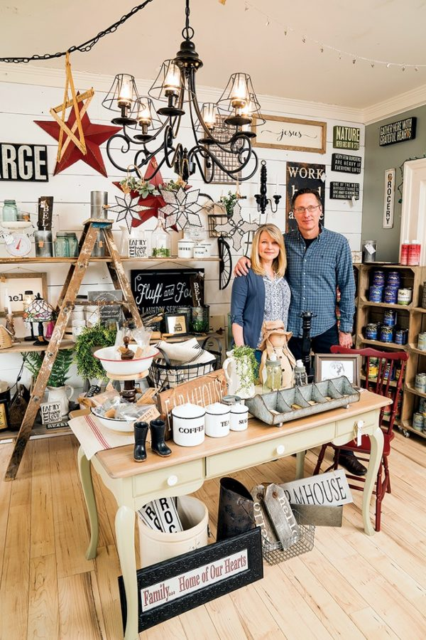 A couple stands inside a vintage goods store.
