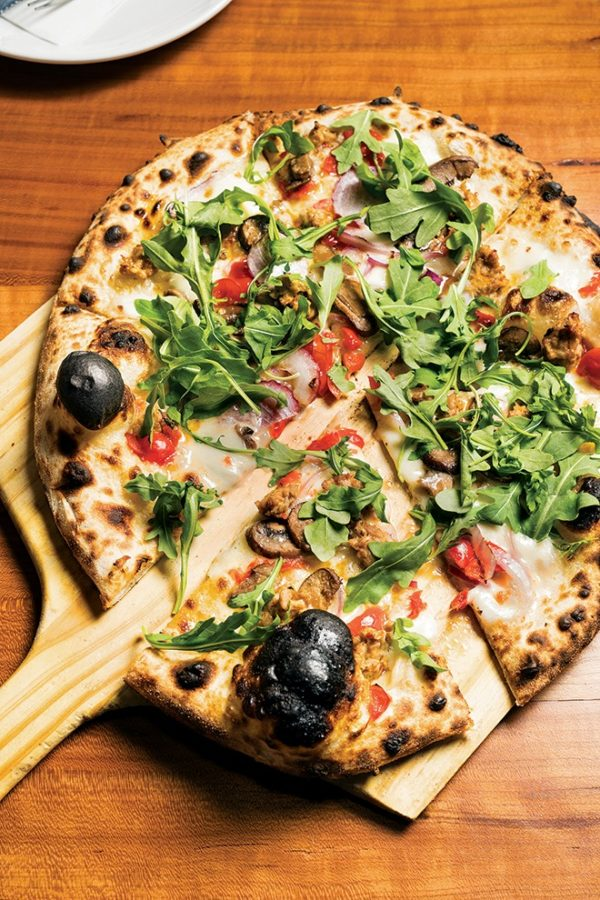 A perfectly charred pizza sits atop a pizza paddle and is dressed with arugula.