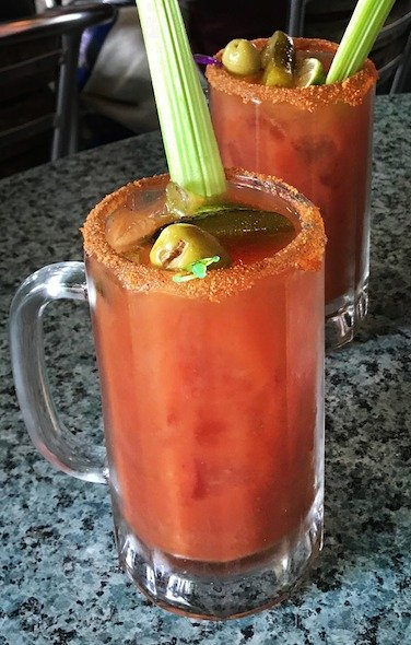 A large mug of Bloody Mary garnished with the requisite celery stalk.