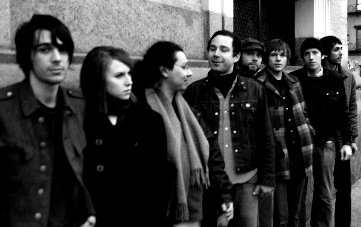 Black and white photo of members of the band along a city street.