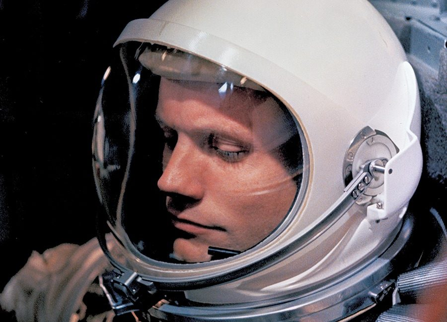 A man sits with a space helmet and suit on.