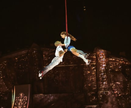 Two trapeze artists dangle midair at a stage performance.