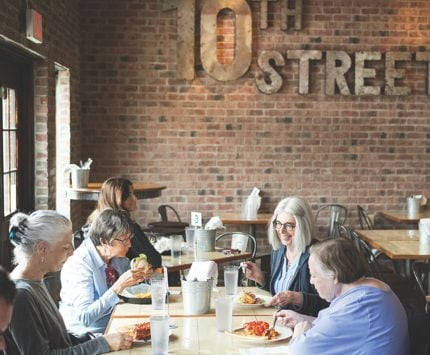 Women sit inside a restaurant adorned with brick walls and enjoy a meal.